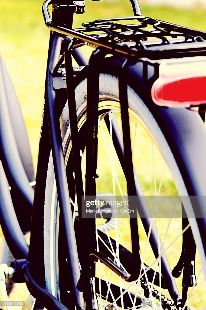 Cropped Image Of Bicycle On Field : Stock Photo