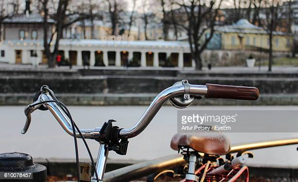 Cropped Image Of Bicycle Parked By Railing In City
