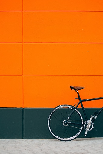 Cropped Image Of Bicycle Parked On Footpath By Orange Wall - gettyimageskorea