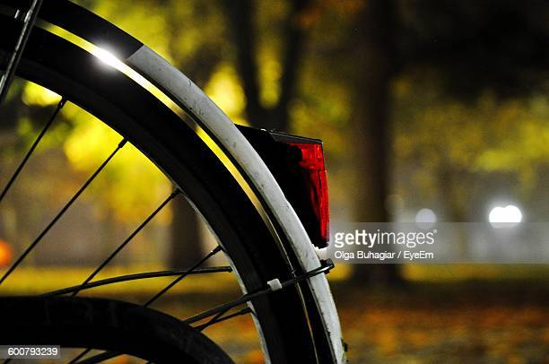 Cropped Image Of Bicycle Wheel With Red Reflector In Park