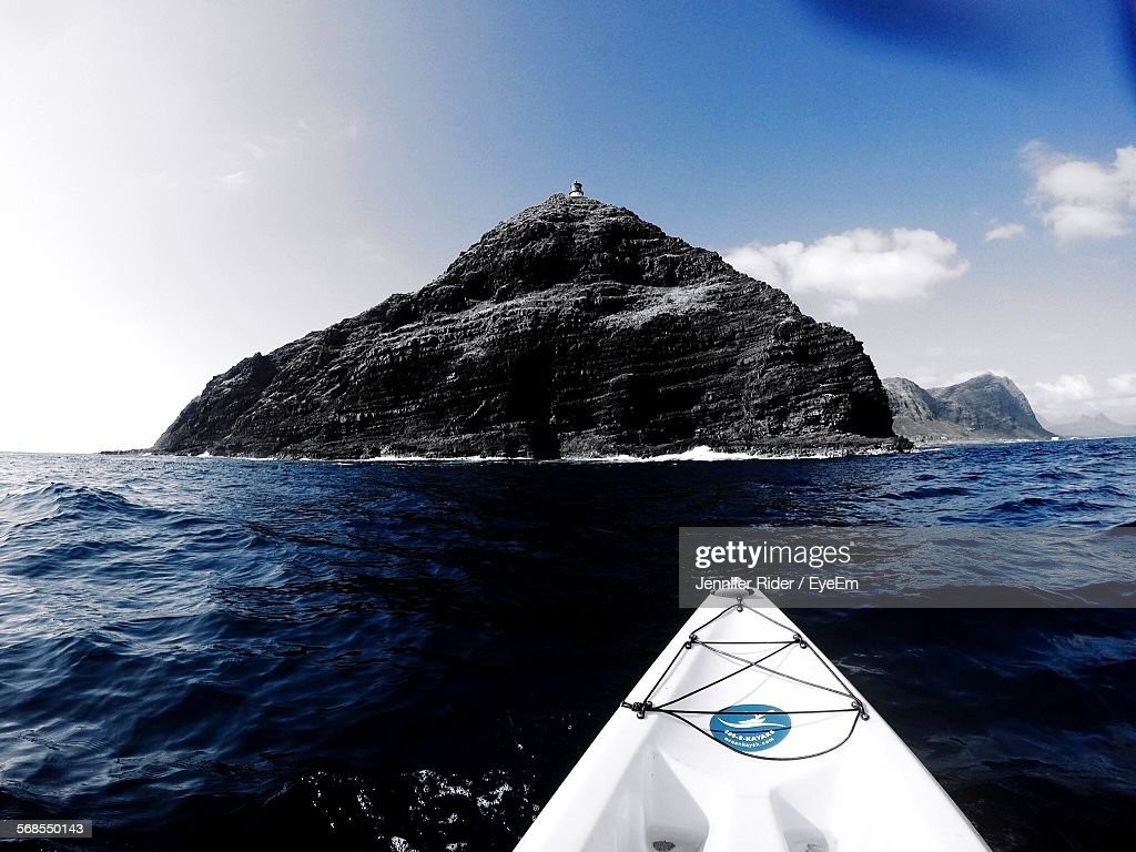 Cropped Image Of Boat In Pacific Ocean Against Mountain : Stock Photo