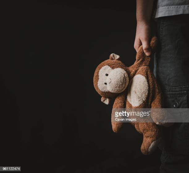 cropped image of boy holding stuffed toy while standing against black background - stuffed toy stock pictures, royalty-free photos & images