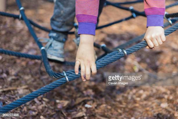 cropped image of boy playing on jungle gym - ジャングルジム ストックフォトと画像