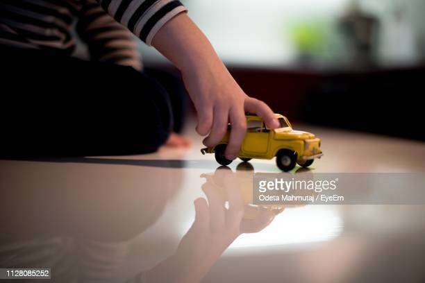 cropped image of boy playing with toy car at home - toy car stock pictures, royalty-free photos & images
