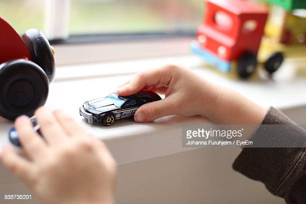 Cropped Image Of Boy Playing With Toy Car At Home