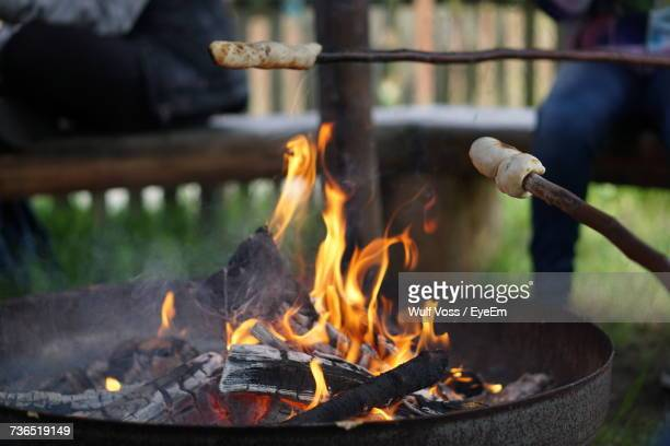 cropped image of breads on sticks at fire pit - stick stock-fotos und bilder