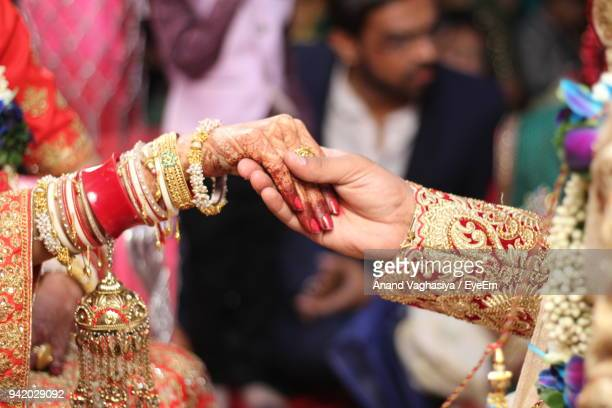 cropped image of bride and bridegroom holding hands - indian bride stock photos and pictures