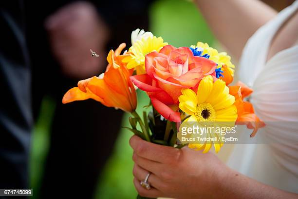 Cropped Image Of Bride Holding Flowers During Wedding Ceremony