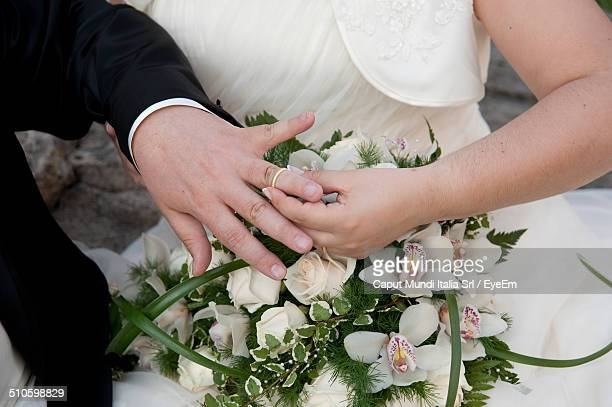 cropped image of bride placing ring on groom in wedding ceremony - putting stock pictures, royalty-free photos & images