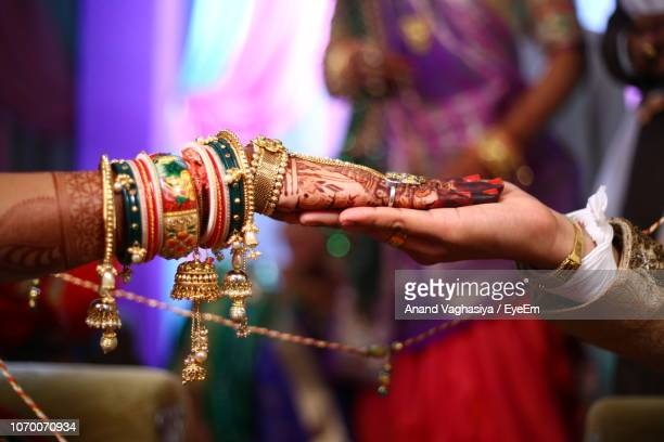 cropped image of bride touching groom hand during wedding ceremony - newlywed stock pictures, royalty-free photos & images