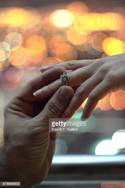 Cropped Image Of Bridegroom Putting Ring On Bride Finger