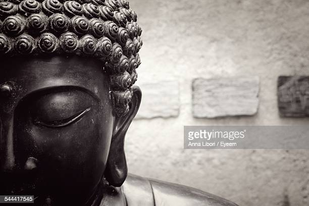 Cropped Image Of Buddha Statue Against Wall