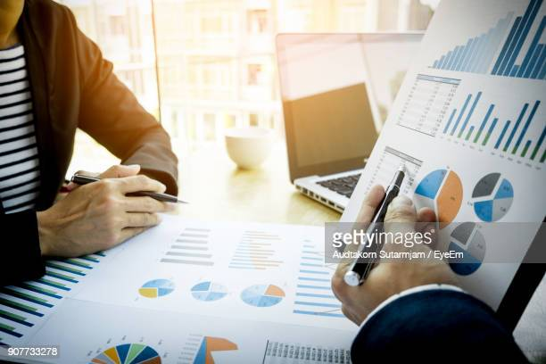 Cropped Image Of Business People Discussing Over Graphs At Table In Office