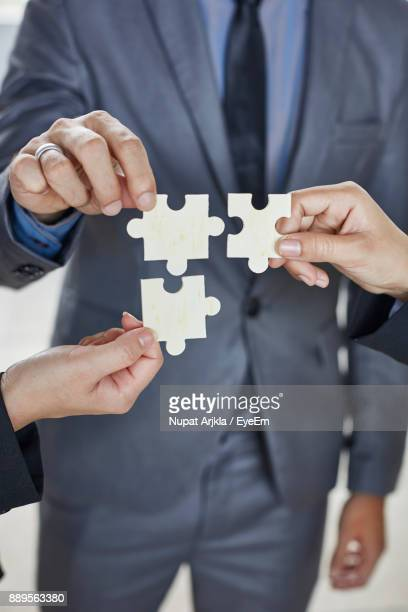 cropped image of business people holding jigsaw puzzles at office - teilabschnitt stock-fotos und bilder