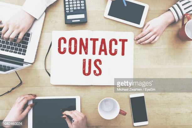 cropped image of business people with technologies amidst contact us text on desk - contact us stock pictures, royalty-free photos & images