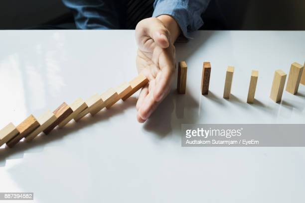 cropped image of businessman playing domino at desk in office - solution stock pictures, royalty-free photos & images