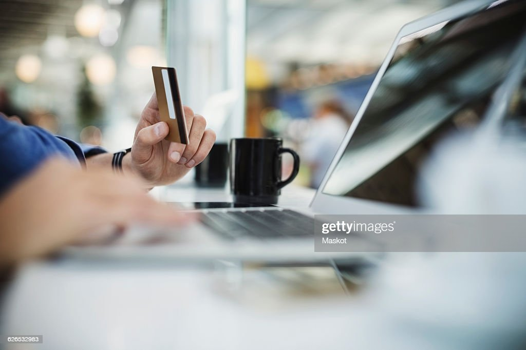 Cropped image of businessman using credit card and laptop at airport lobby : Stock Photo