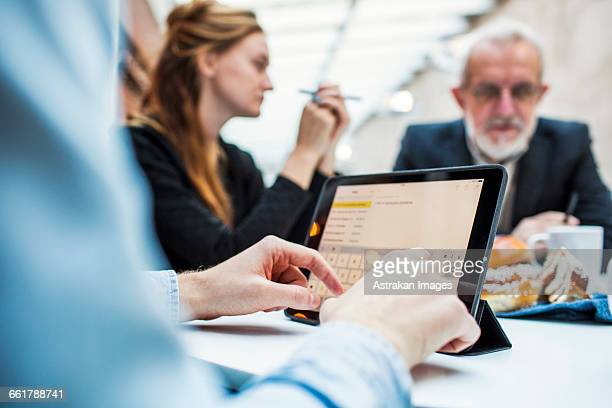 Cropped image of businessman using digital tablet with colleagues in background at office