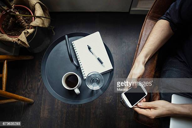 Cropped image of businessman using phone while sitting by drinks and spiral notebook