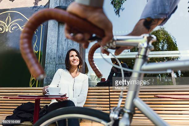 Cropped image of businessman with bicycle talking to colleague at sidewalk cafe