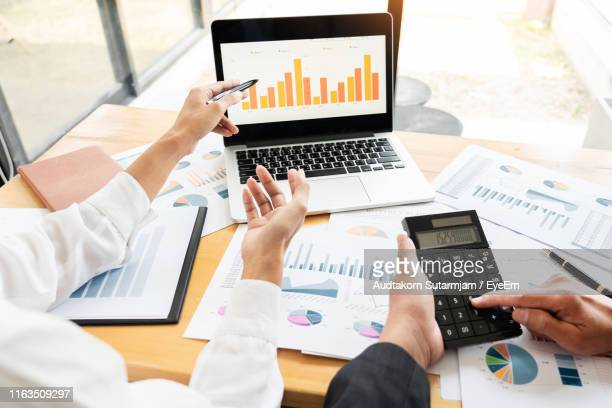 cropped image of businessman with coworker discussing with documents and technologies in meeting - annual report stock pictures, royalty-free photos & images