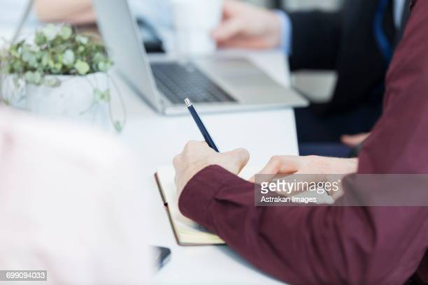 Cropped image of businessman writing in book in meeting