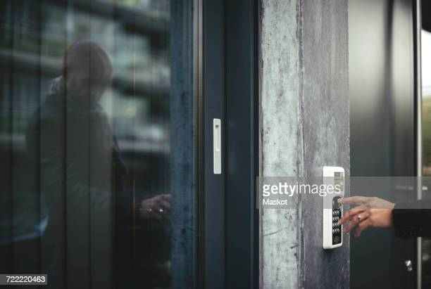cropped image of businessmans hand entering security code to open office door - security code stock photos and pictures