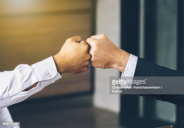 cropped image of businessmen bumping fist at office - fist bump stock pictures, royalty-free photos & images