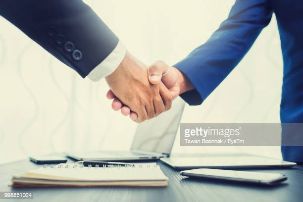 Cropped Image Of Businessmen Shaking Hands At Table