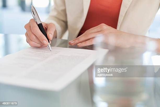 cropped image of businesswoman signing paperwork - signature stock photos and pictures