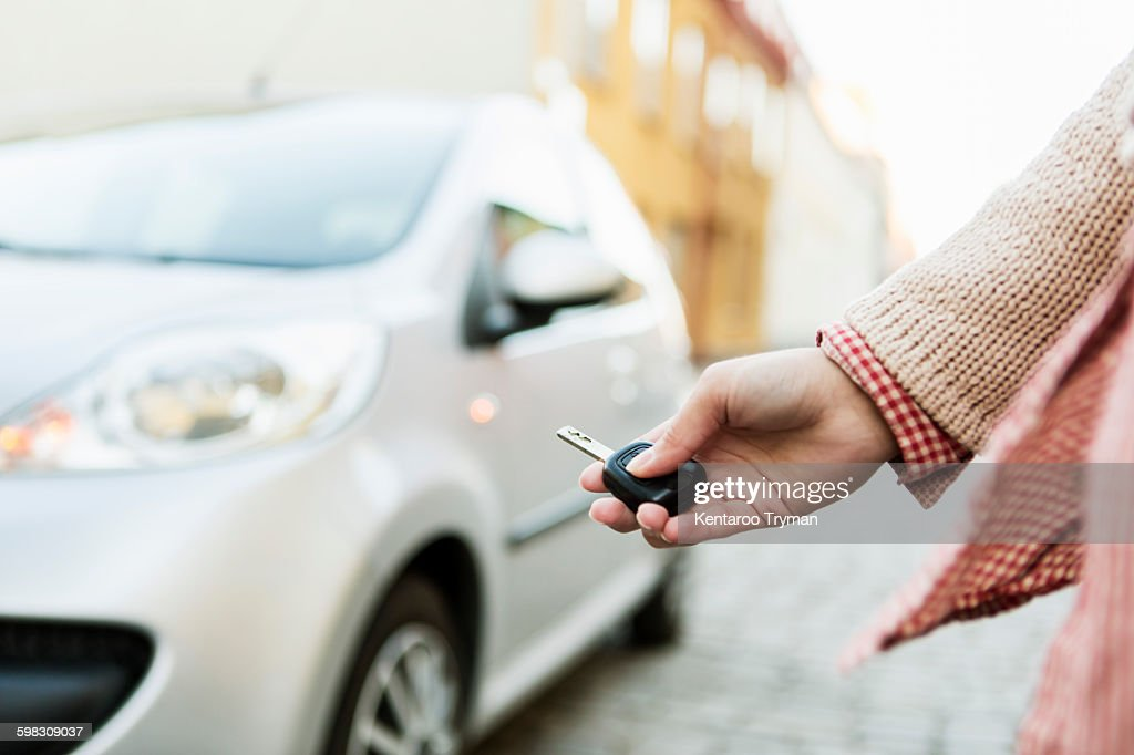 Cropped image of businesswoman using remote control key to unlock car : Stock Photo