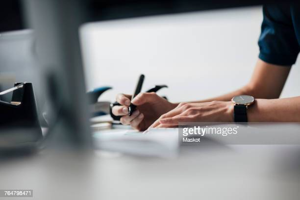 cropped image of businesswoman writing at desk in office - stift stock-fotos und bilder