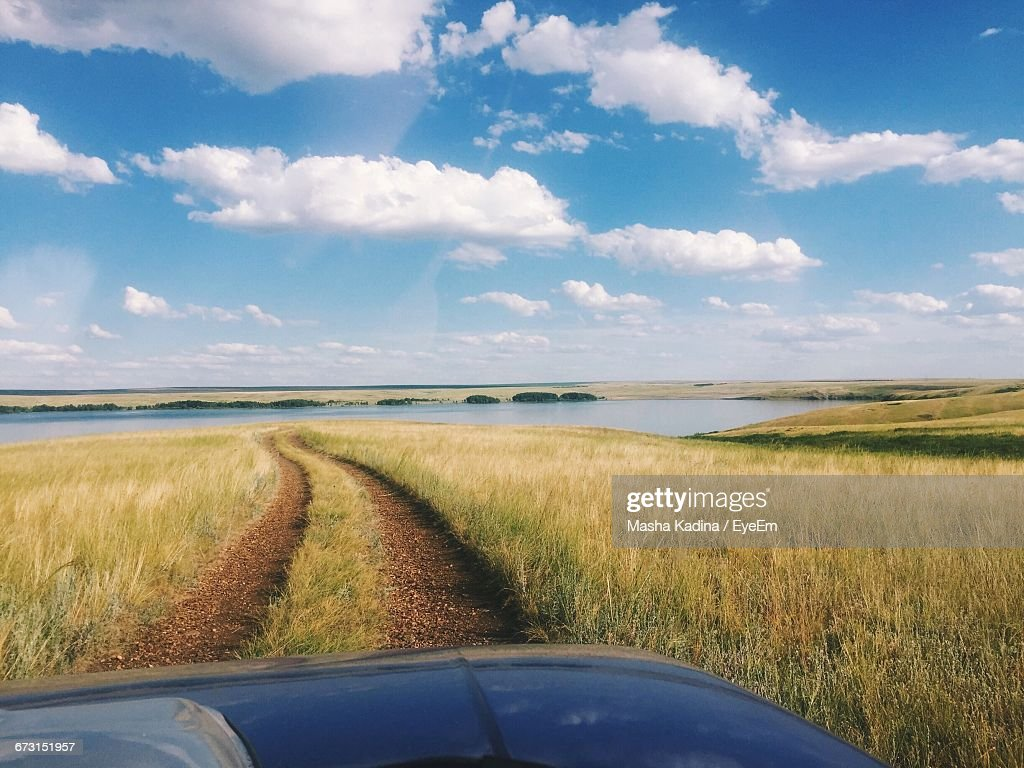 Cropped image of car on grassy field by lake against sky stock photo cropped image of car on grassy field by lake against sky voltagebd Images