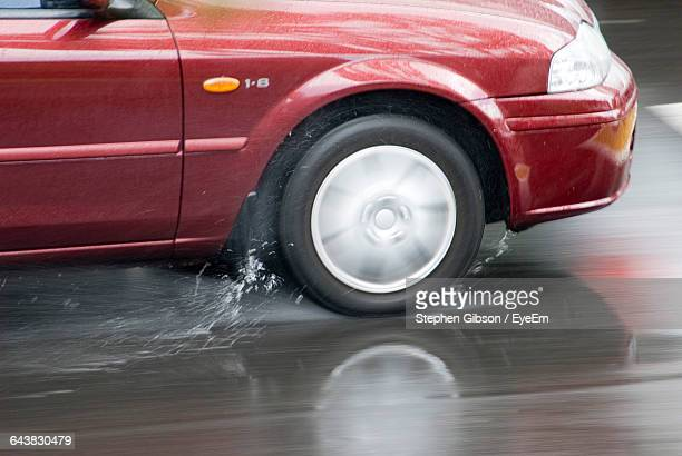 Cropped Image Of Car On Wet Road During Monsoon