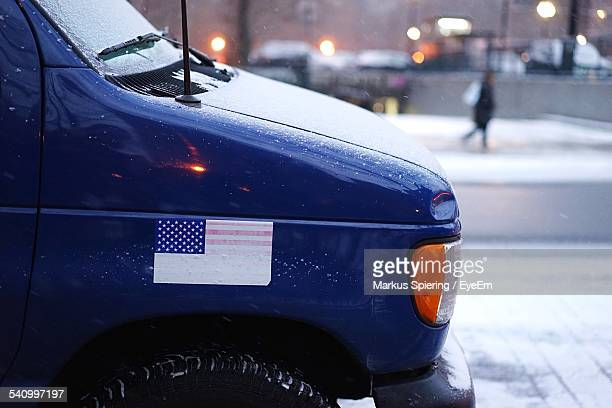 cropped image of car with american flag on street during winter - bumper sticker stock photos and pictures