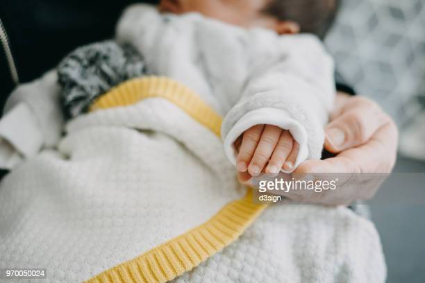 Cropped image of caring grandmother holding the hand of new born baby at home