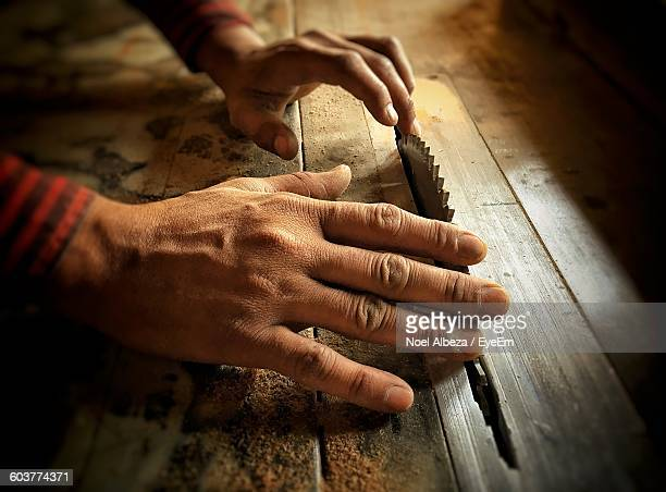 Cropped Image Of Carpenter Sawing With Blade