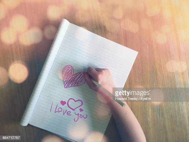 Cropped Image Of Child Drawing Heart Shape On Book At Table