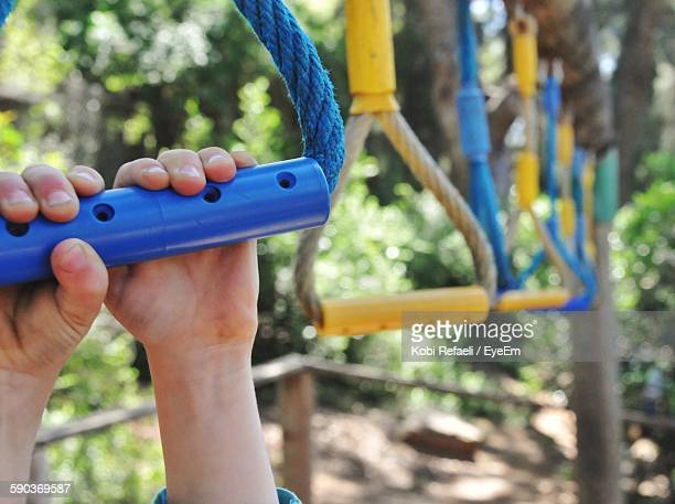 cropped image of child holding monkey bar at park - ジャングルジム ストックフォトと画像