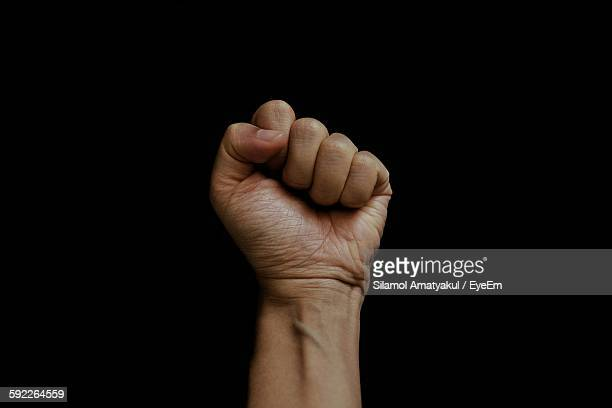 cropped image of clenched fist against black background - fist stock pictures, royalty-free photos & images