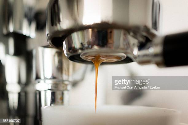 Cropped Image Of Coffee Maker Pouring In Cup At Cafe