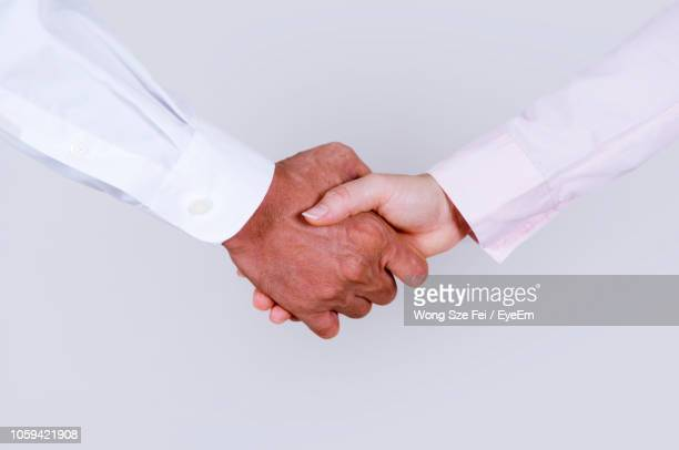 cropped image of colleagues shaking hands against white background - sleeve stock pictures, royalty-free photos & images