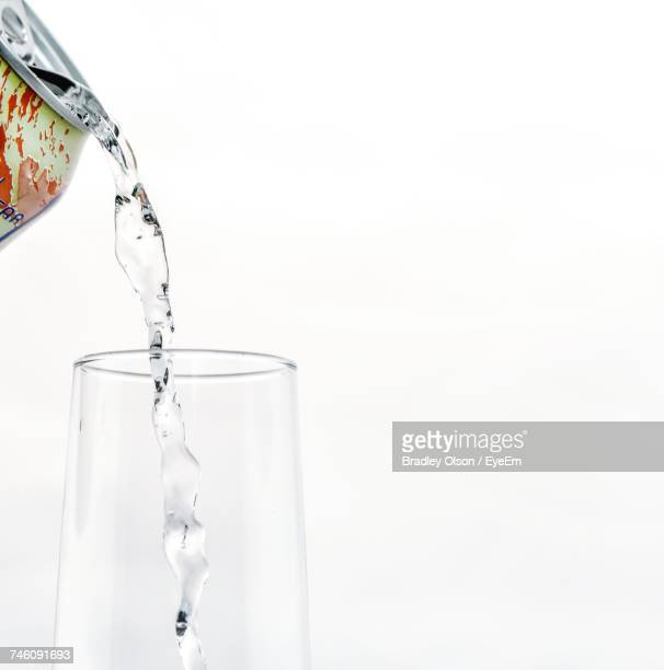 Cropped Image Of Container Pouring Soda In Glass Against White Background