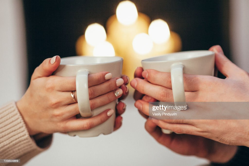 Cropped image of couple holding coffee cups against illuminated candles at home : Foto de stock