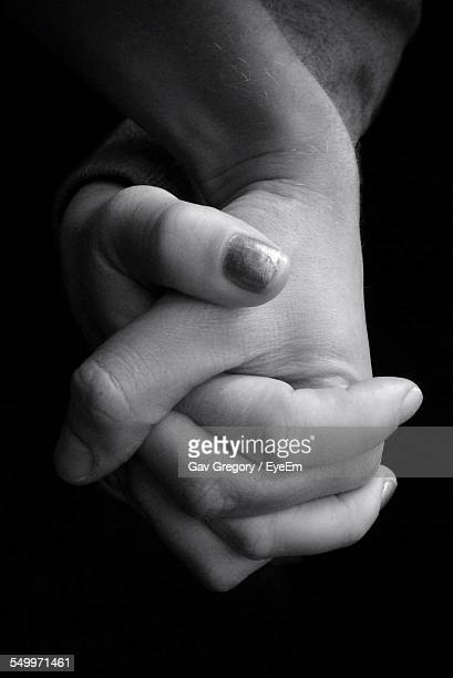 Cropped Image Of Couple Holding Hands Against Black Background