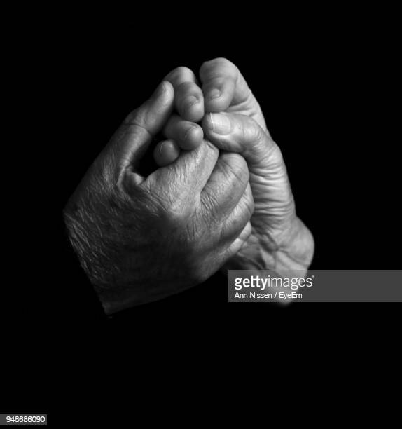 cropped image of couple holding hands against black background - black and white hands stock pictures, royalty-free photos & images