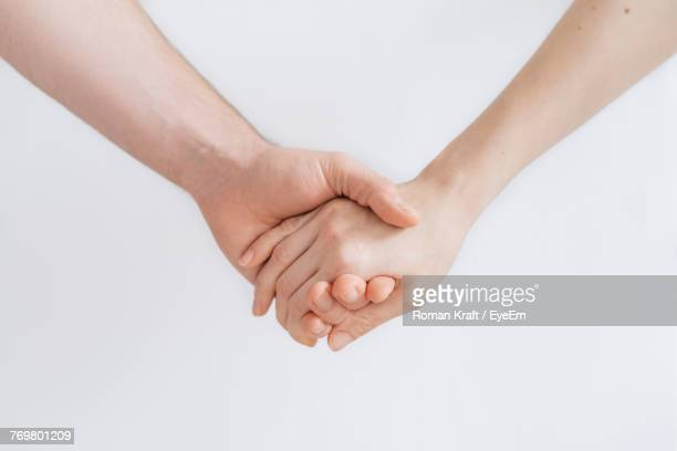 cropped image of couple holding hands against white background - de mãos dadas - fotografias e filmes do acervo