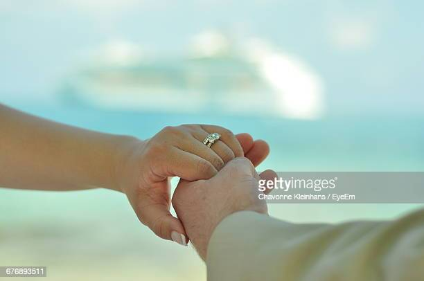 Cropped Image Of Couple Holding Hands At Beach