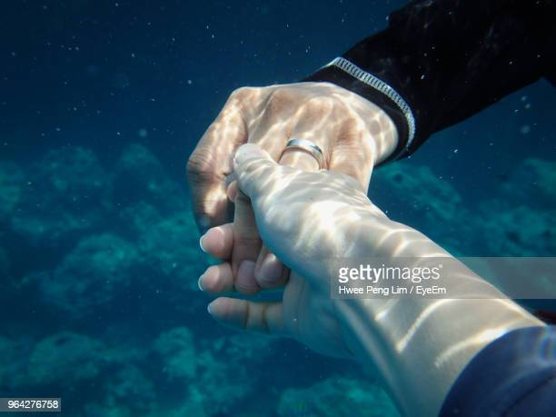 Cropped Image Of Couple Holding Hands Undersea