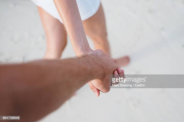 Cropped Image Of Couple Holding Hands While Walking At Beach